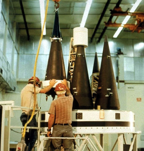 U.S. technicians secure reentry vehicles housing warheads to a MIRV bus